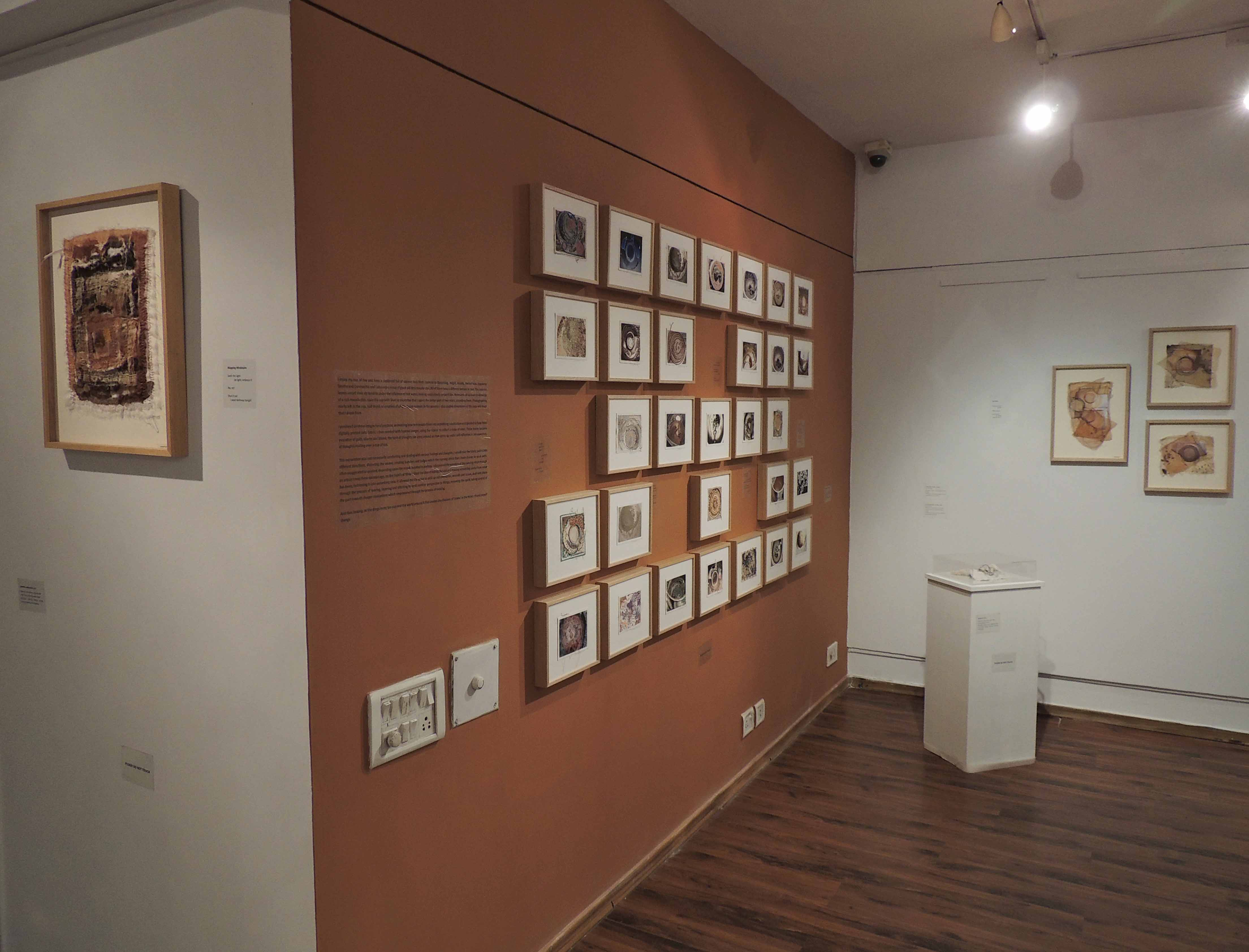 Image 14 : Display image of The Piercing Needle, Works in view: Left- Mapping Mindstains, Centre [on coloured wasll]The Universe in My Tea Cup [set of 30 works], Right: Wired Up, Far Right: A Careless Hand Poured [set of three works], Photo credit: gopika nath